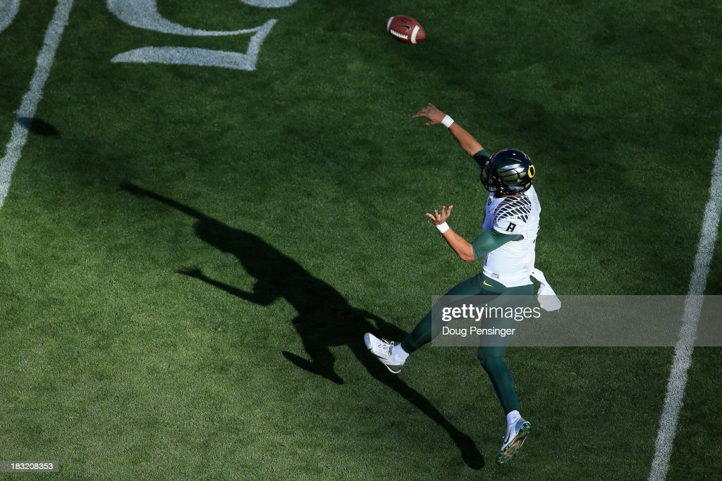 quarterback <a gi-track='captionPersonalityLinkClicked' href=/galleries/search?phrase=Marcus+Mariota&family=editorial&specificpeople=8572256 ng-click='$event.stopPropagation()'>Marcus Mariota</a> #8 of the Oregon Ducks delivers a pass against the Colorado Buffaloes at Folsom Field on October 5, 2013 in Boulder, Colorado. The Ducks defeated the Buffs 57-16.