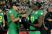 Quarterback Marcus Mariota of the Oregon Ducks hands the Leishman Trophy to linebacker Tony Washington after defeating the Florida State Seminoles...