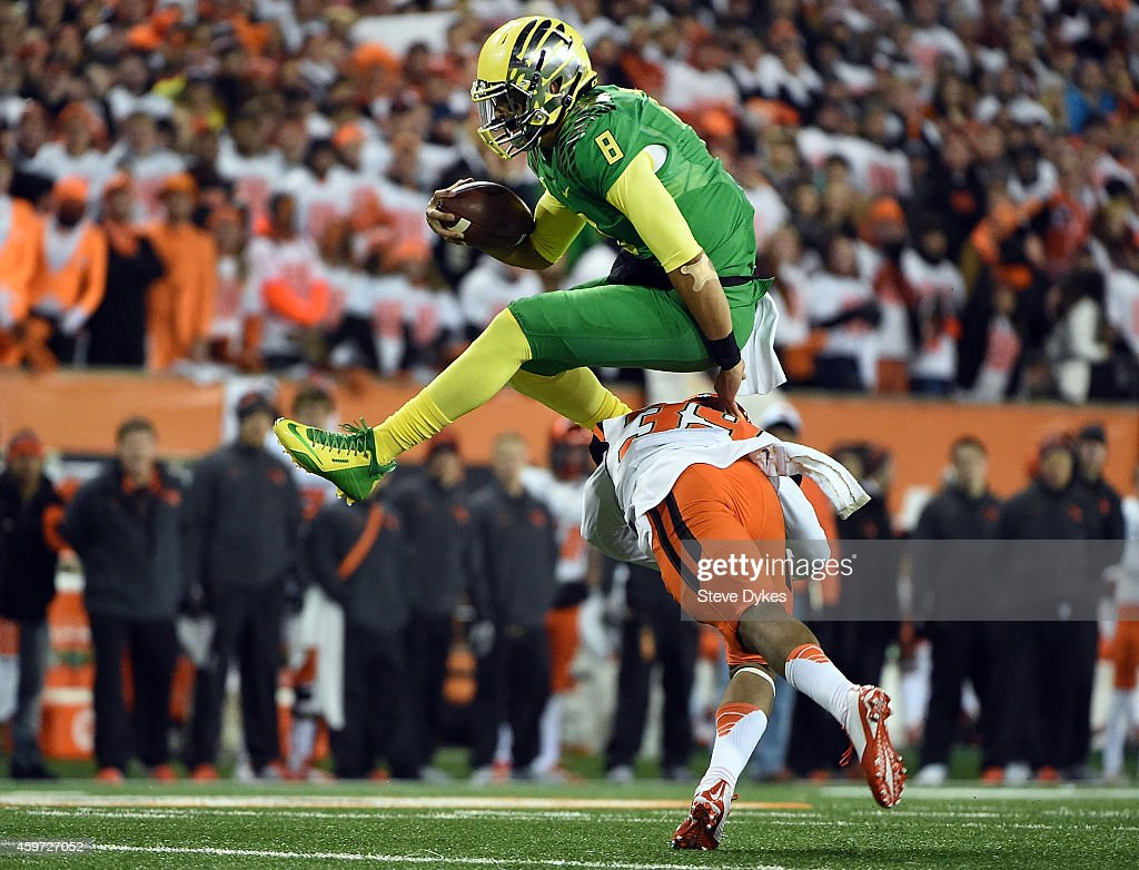 Quarterback Marcus Mariota of the Oregon Ducks hurdles safety Justin Strong of the Oregon State Beavers during the first quarter of the game at Reser...