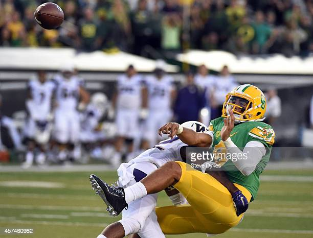 Quarterback Marcus Mariota of the Oregon Ducks is hit by defensive back Budda Baker of the Washington Huskies as he passes th ball during the second...