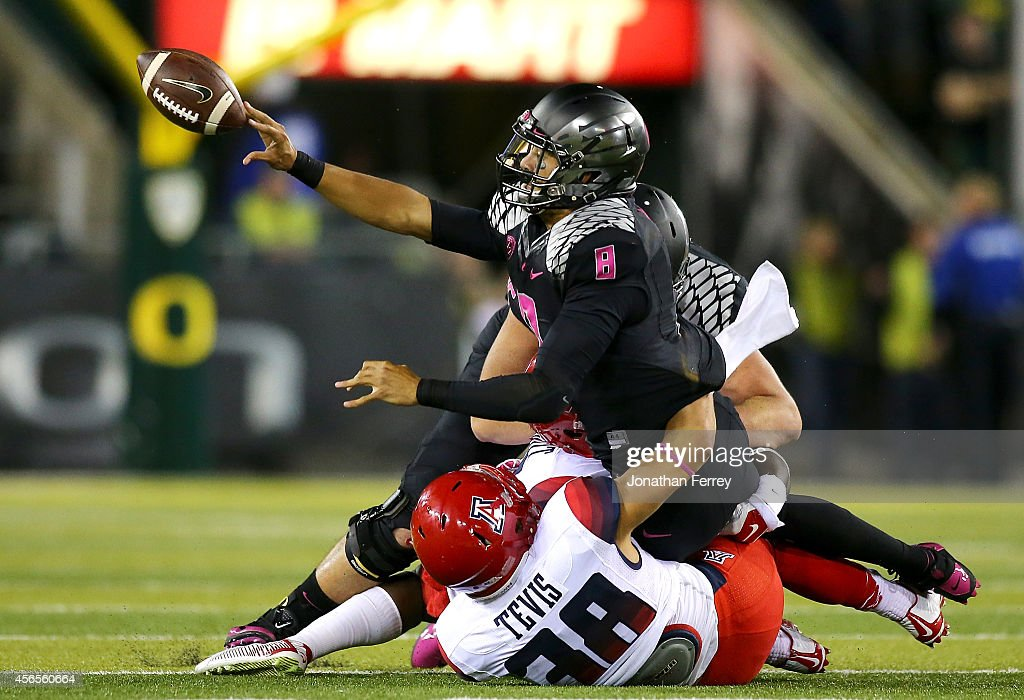 Quarterback Marcus Mariota of the Oregon Ducks pitches the ball while being tackled by Jared Tevis of the Arizona Wildcats at Autzen Stadium on...