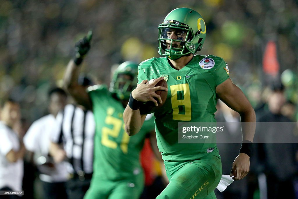 Quarterback <a gi-track='captionPersonalityLinkClicked' href=/galleries/search?phrase=Marcus+Mariota&family=editorial&specificpeople=8572256 ng-click='$event.stopPropagation()'>Marcus Mariota</a> #8 of the Oregon Ducks runs for a 23-yard touchdown in the fourth quarter of the College Football Playoff Semifinal at the Rose Bowl Game presented by Northwestern Mutual at the Rose Bowl on January 1, 2015 in Pasadena, California.
