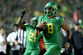 Quarterback Marcus Mariota of the Oregon Ducks runs for a 23yard touchdown in the fourth quarter of the College Football Playoff Semifinal at the...