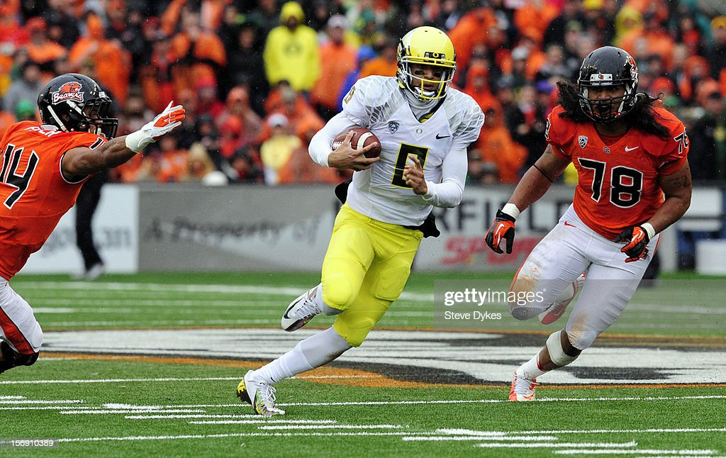 Quarterback <a gi-track='captionPersonalityLinkClicked' href=/galleries/search?phrase=Marcus+Mariota&family=editorial&specificpeople=8572256 ng-click='$event.stopPropagation()'>Marcus Mariota</a> #8 of the Oregon Ducks runs past cornerback Jordan Poyer #14 and defensive end Rudolf Fifita #78 of the Oregon State Beavers in the fourth quarter of the game on November 24, 2012 at Reser Stadium in Corvallis, Oregon.