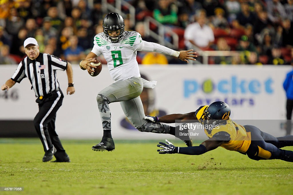 Quarterback Marcus Mariota of the Oregon Ducks steps out of the grasp of defensive end Jonathan Johnson of the California Golden Bears in the third...