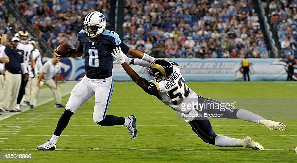 Quarterback Marcus Mariota of the Tennessee Titans evades the grasp of Alec Ogletree of the St Louis Rams during the first half of a game at Nissan...