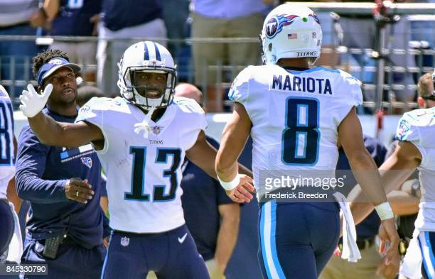 Quarterback Marcus Mariota of the Tennessee Titans is congratulated by teammate Taywan Taylor after running in a touchdown against the Oakland...