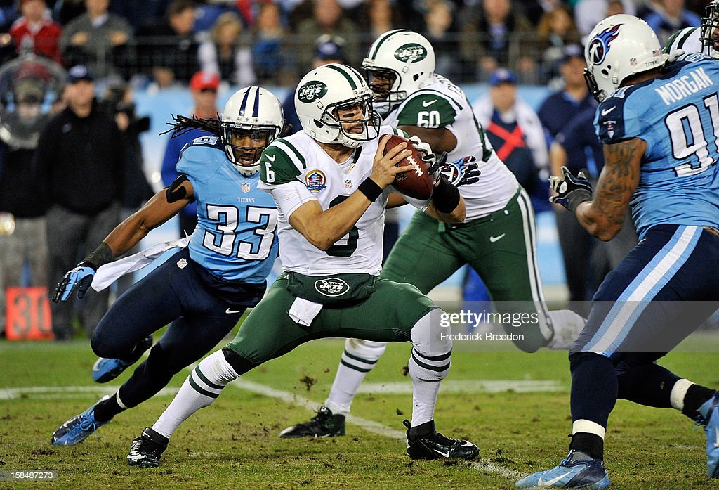 Quarterback <a gi-track='captionPersonalityLinkClicked' href=/galleries/search?phrase=Mark+Sanchez&family=editorial&specificpeople=690406 ng-click='$event.stopPropagation()'>Mark Sanchez</a> #6 of the New York Jets is pressured by Michael Griffin #33 of the Tennessee Titans at LP Field on December 17, 2012 in Nashville, Tennessee.