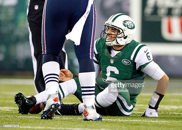 Quarterback Mark Sanchez of the New York Jets reacts after getting sacked by the New England Patriots during a game at MetLife Stadium on November 22...
