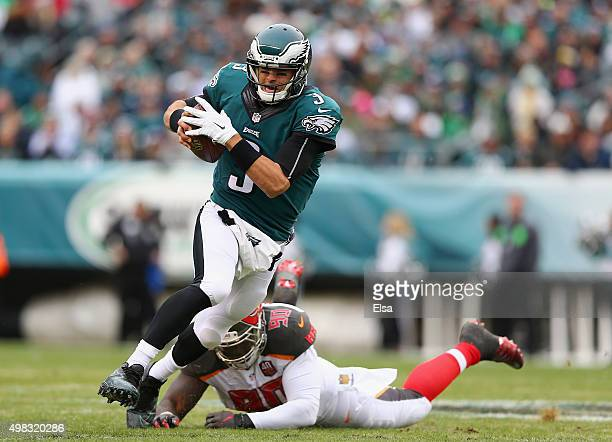 Quarterback Mark Sanchez of the Philadelphia Eagles scrambles against Henry Melton of the Tampa Bay Buccaneers in the first quarter at Lincoln...