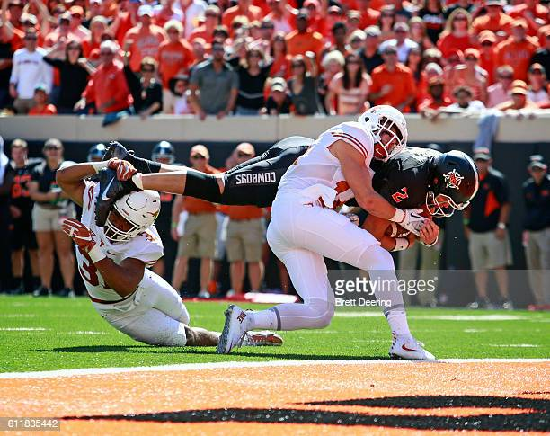 Quarterback Mason Rudolph of the Oklahoma State Cowboys is hit by safety Dylan Haines and safety Jason Hall of the Texas Longhorns on his way to...