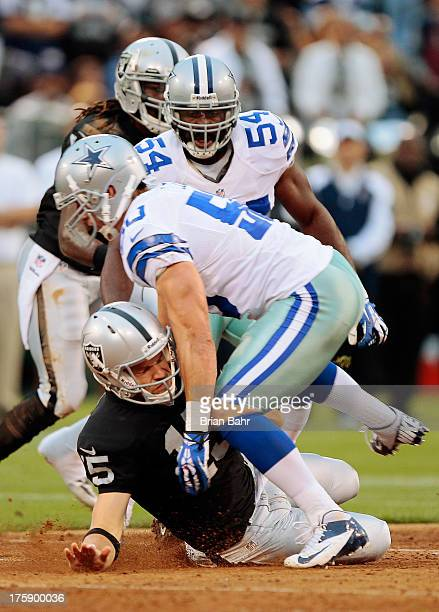 Quarterback Matt Flynn of the Oakland Raiders narrowly avoids a knee to the head as he slides to avoid a tackle by linebacker Sean Lee of the Dallas...