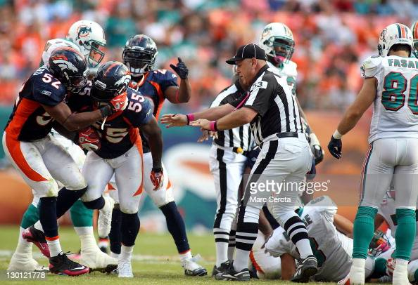 Quarterback Matt Moore of the Miami Dolphins fumbles as Linebacker DJ Williams of the Denver Broncos recovers at Sun Life Stadium on October 23 2011...