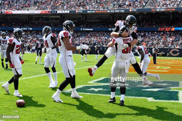 Quarterback Matt Ryan of the Atlanta Falcons celebrates with Austin Hooper after Hooper scored a touchdown in the fourth quarter against the Chicago...