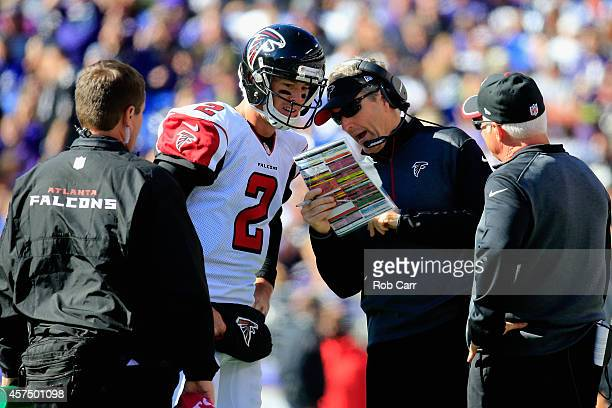 Quarterback Matt Ryan of the Atlanta Falcons talks with offensive coordinator Dirk Koetter and head coach Mike Smith in the first half of a game...