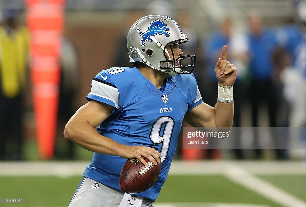 Quarterback Matt Stafford #9 of the Detroit Lions rolls out to avoide the rush of Chris Smith #98 during the first quarter of the preseason game against the Jacksonville Jaguars at Ford Field on August 22, 2014 in Detroit, Michigan. The Lions defeated the Jaguars 13-12.