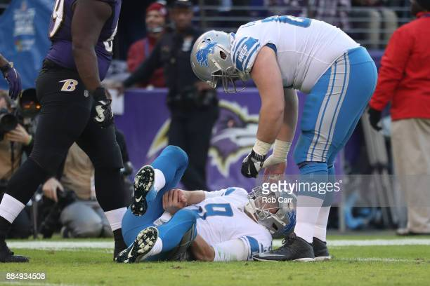 Quarterback Matthew Stafford of the Detroit Lions grabs his hand after being tackled in the fourth quarter against the Baltimore Ravens at MT Bank...