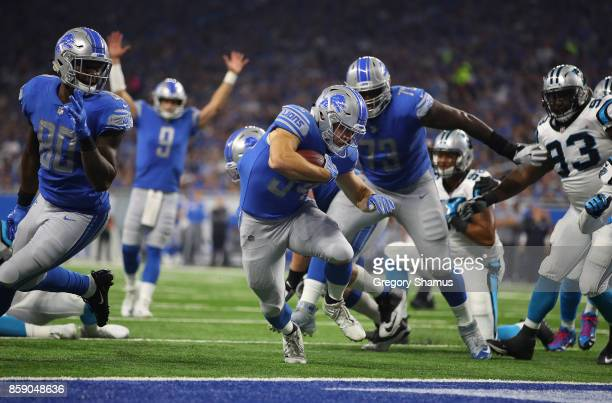 Quarterback Matthew Stafford of the Detroit Lions signals a touchdown as running back Zach Zenner crosses the goal line against the Carolina Panthers...