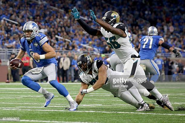 Quarterback Matthew Stafford of the Detroit Lions tries to avoid the tackle of Dante Fowler of the Jacksonville Jaguars and Jared Odrick of the...