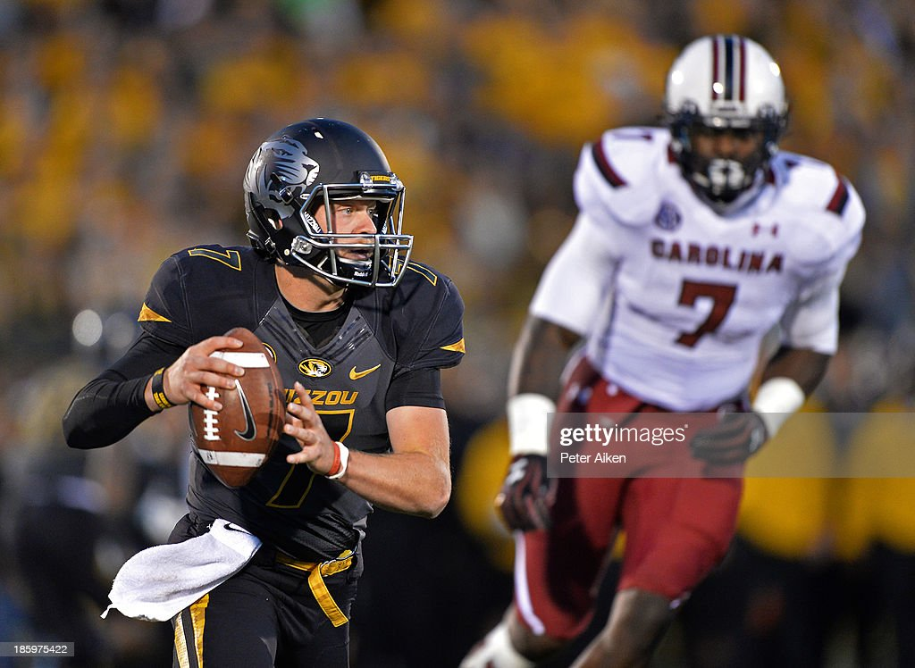 Quarterback Maty Mauk #7 of the Missouri Tigers scrambles up field against pressure from defensive end Jadeveon Clowney #7 of the South Carolina Gamecocks during the first half on October 26, 2013 at Faurot Field/Memorial Stadium in Columbia, Missouri.