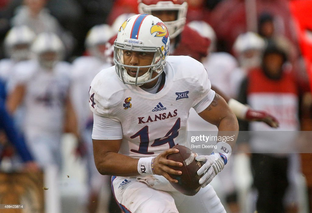 Quarterback Michael Cummings #14 of the Kansas Jayhawks scrambles in the backfield against the Oklahoma Sooners November 22, 2014 at Gaylord Family-Oklahoma Memorial Stadium in Norman, Oklahoma. The Sooners defeated the Jayhawks 44-7.