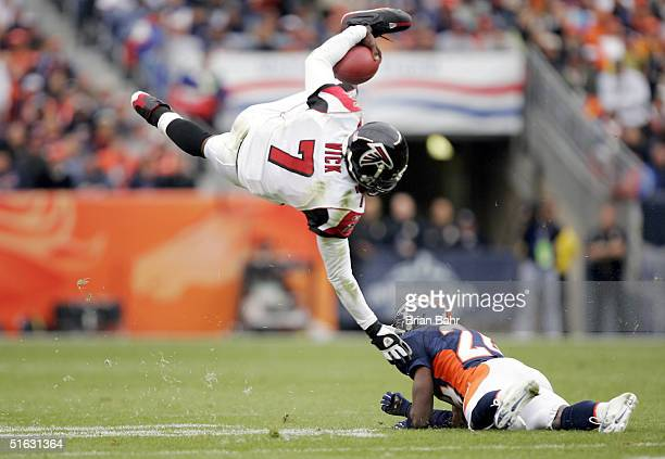 Quarterback Michael Vick of the Atlanta Falcons flips over cornerback Champ Bailey of the Denver Broncos for a first down on fourth and one from the...