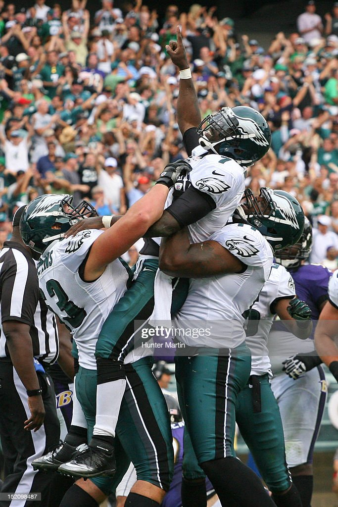 Quarterback <a gi-track='captionPersonalityLinkClicked' href=/galleries/search?phrase=Michael+Vick&family=editorial&specificpeople=201746 ng-click='$event.stopPropagation()'>Michael Vick</a> #7 of the Philadelphia Eagles celebrates scoring a touchdown with guard Danny Watkins #63 and tackle Demetress Bell #77 during a game against the Baltimore Ravens on September 17, 2012 at Lincoln Financial Field in Philadelphia, Pennsylvania.