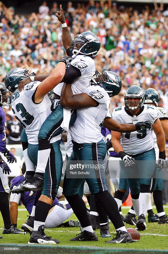 Quarterback <a gi-track='captionPersonalityLinkClicked' href=/galleries/search?phrase=Michael+Vick&family=editorial&specificpeople=201746 ng-click='$event.stopPropagation()'>Michael Vick</a> #7 of the Philadelphia Eagles is lifted by teammates Danny Watkins #63 and Demetress Bell #77 after Vick ran for a six yard touchdown in the fourth quarter against the Baltimore Ravens during a game at Lincoln Financial Field on September 16, 2012 in Philadelphia, Pennsylvania. The Eagles defeated the Ravens 24-23.