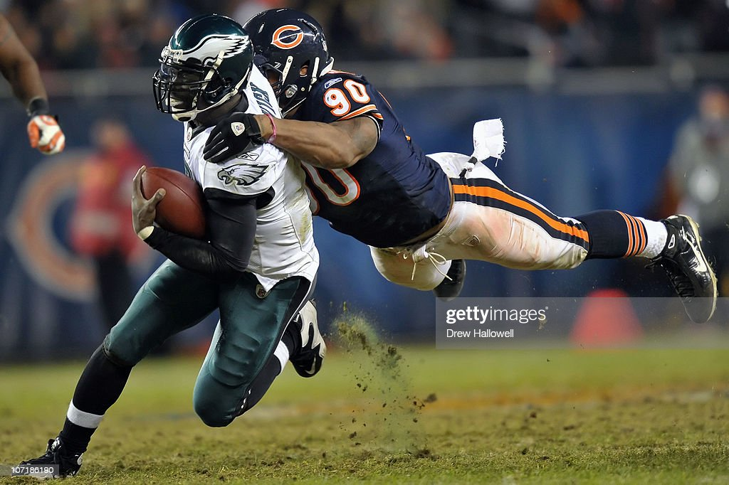Quarterback Michael Vick of the Philadelphia Eagles is tackled by defensive end Julius Peppers of the Chicago Bears at Soldier Field on November 28...