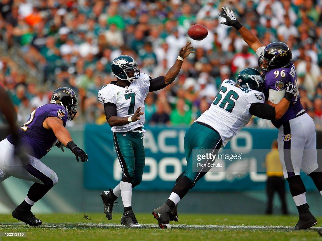 Quarterback Michael Vick of the Philadelphia Eagles makes a pass as teammate Dallas Reynolds blocks Maake Kemoeatu of the Baltimore Ravens as Haloti...