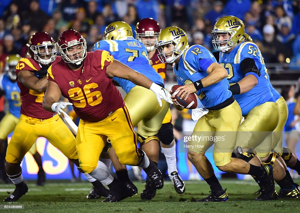 Quarterback Mike Fafaul #12 of the UCLA Bruins scrambles out of the pocket as he is chased by defensive tackle Stevie Tu'ikolovatu #96 of the USC Trojans during the first quarter at Rose Bowl on November 19, 2016 in Pasadena, California.