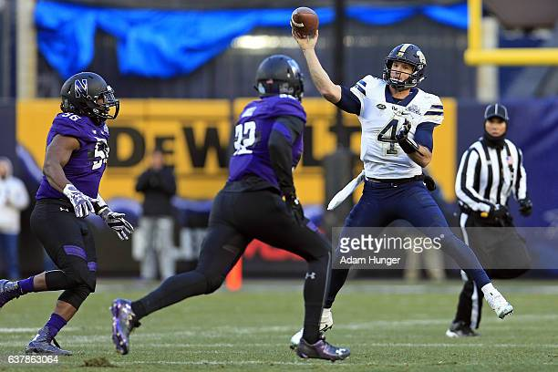 Quarterback Nathan Peterman of the Pittsburgh Panthers passes under pressure from linebacker Nate Hall of the Northwestern Wildcats during the New...