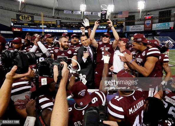 Quarterback Nick Fitzgerald of the Mississippi State Bulldogs hoists the MVP trophy after his team won 1716 over the Miami Redhawks in the St...