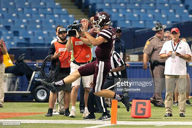 Quarterback Nick Fitzgerald of the Mississippi State Bulldogs out runs Tony Reid of the Miami Redhawks' to high step into the endzone for the score...