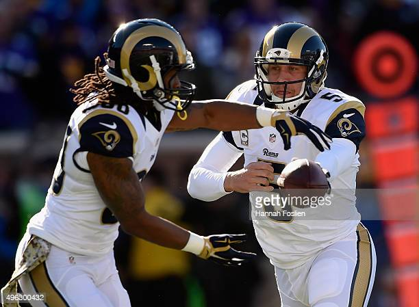 Quarterback Nick Foles of the St Louis Rams hands off the ball to teammate Todd Gurley during the first quarter of the game against the Minnesota...