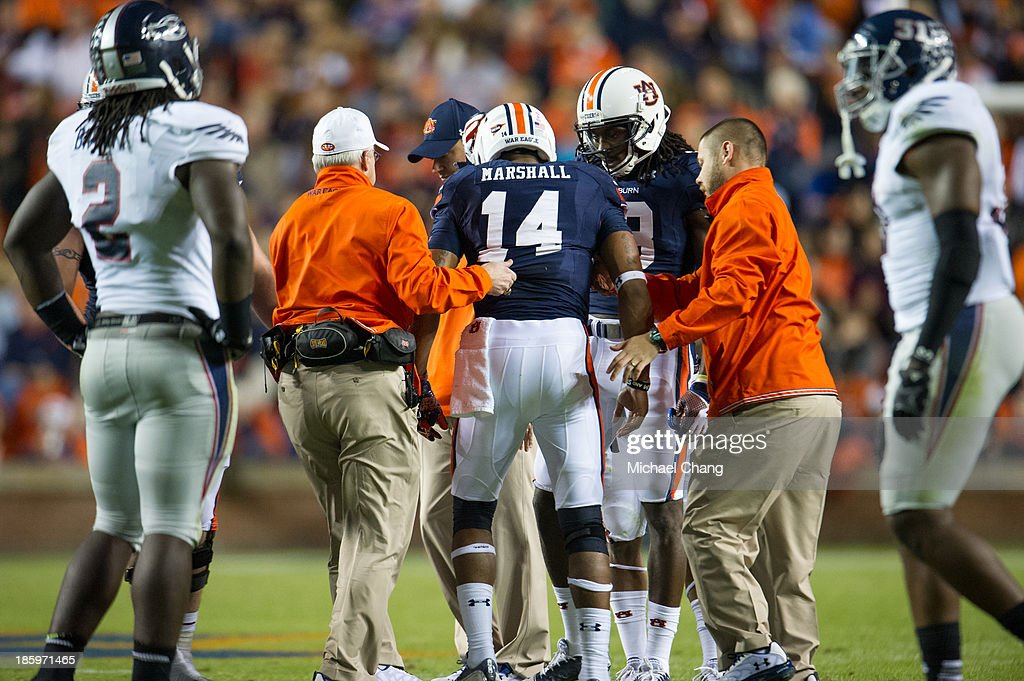 Quarterback Nick Marshall #14 of the Auburn Tigers is helped off the field after being injured during the second quarter of play during their game against the Florida Atlantic Owls on October 26, 2013 at Jordan-Hare Stadium in Auburn, Alabama. At the end of the first quarter Auburn leads Florida Atlantic 21-0.
