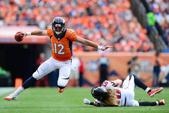 Quarterback Paxton Lynch of the Denver Broncos evades linebacker AJ Hawk of the Atlanta Falcons in the first half of the game at Sports Authority...