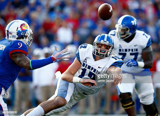 Quarterback Paxton Lynch of the Memphis Tigers releases the ball while scrambling as safety Fish Smithson of the Kansas Jayhawks applies pressure...