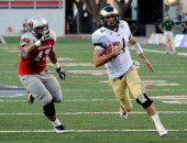 Quarterback Pete Thomas of the Colorado State Rams rushes for a touchdown ahead of Trent AllmangWilder of the UNLV Rebels during their game at Sam...