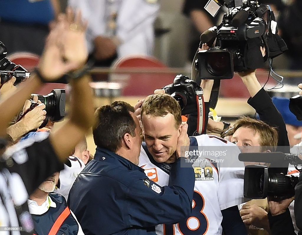 Quarterback Petyton Manning of the Denver Broncos is congratulated in the final moments of Super Bowl 50 against the Carolina Panthers at Levi's Stadium in Santa Clara, California February 7, 2016. Peyton Manning clinched a fairytale second Super Bowl victory as the Denver Broncos produced an astonishing defensive display to defeat the Carolina Panthers 24-10. / AFP / TIMOTHY A. CLARY
