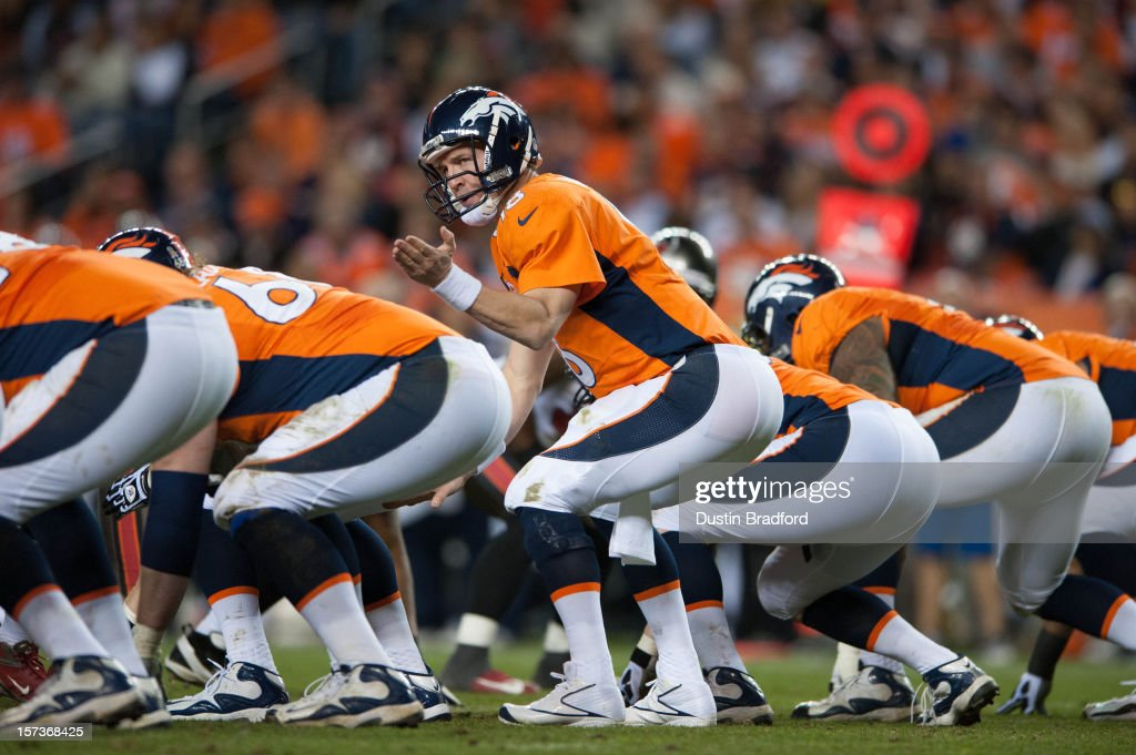 Quarterback <a gi-track='captionPersonalityLinkClicked' href=/galleries/search?phrase=Peyton+Manning&family=editorial&specificpeople=184524 ng-click='$event.stopPropagation()'>Peyton Manning</a> #18 of the Denver Broncos adjusts the play at the line of scrimmage during a game against the Tampa Bay Buccaneers at Sports Authority Field Field at Mile High on December 2, 2012 in Denver, Colorado.