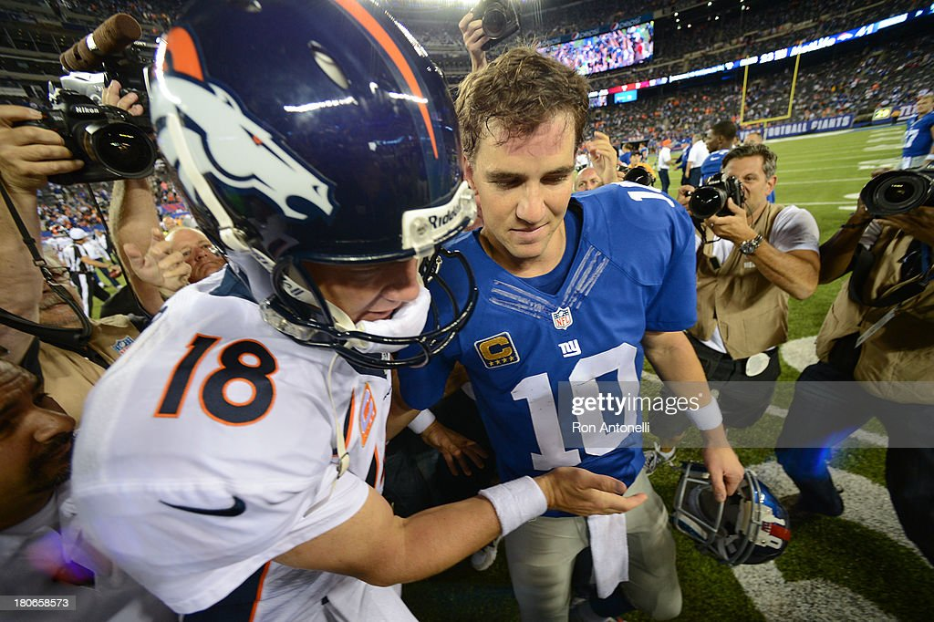 Quarterback Peyton Manning of the Denver Broncos and brother quarterback Eli Manning of the New York Giants shake hands at the end of the Denver...