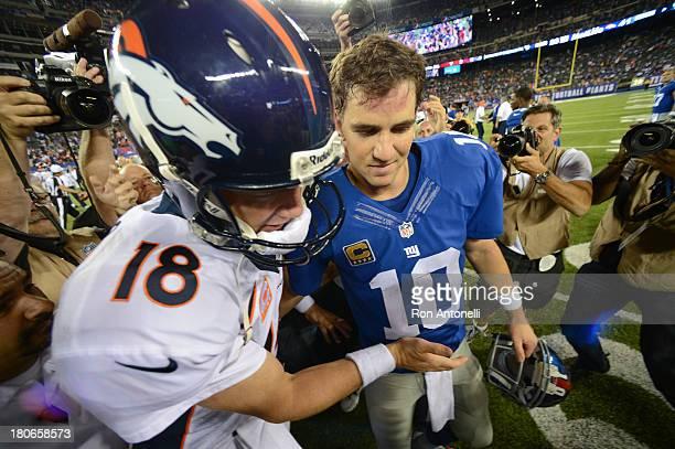 Quarterback Peyton Manning of the Denver Broncos and brother quarterback Eli Manning of the New York Giants shake hands at the end of the Denver...