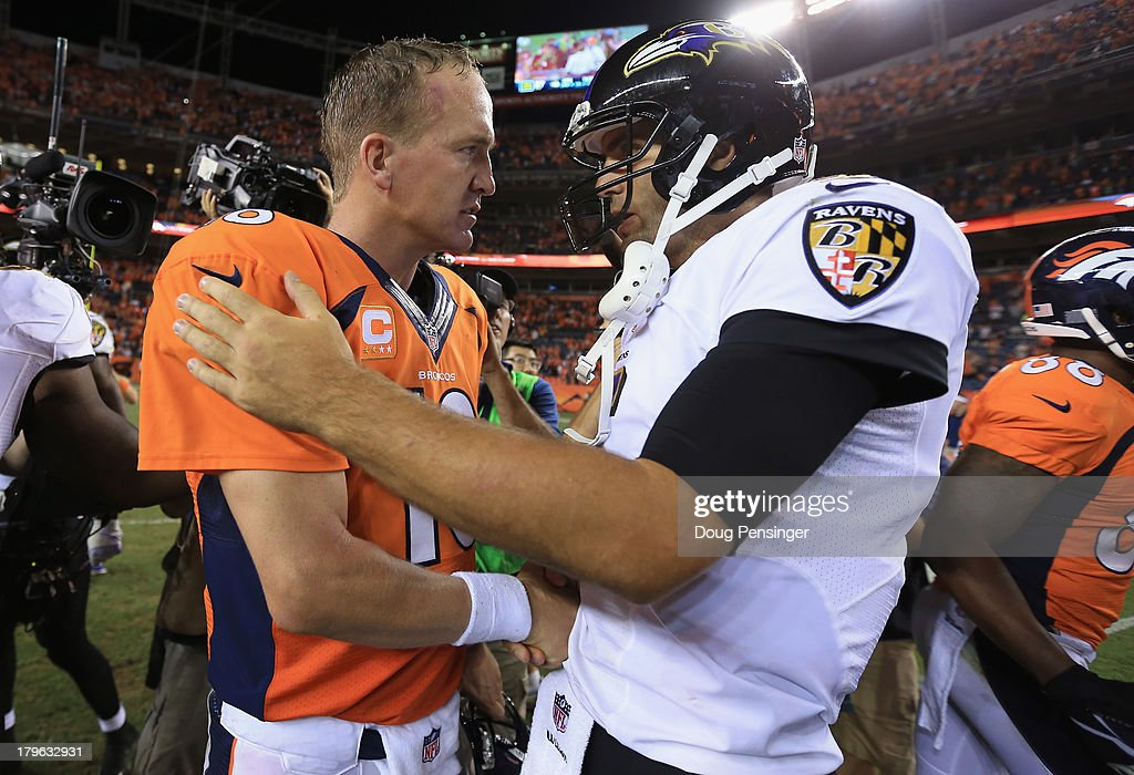 Quarterback Peyton Manning #18 of the Denver Broncos and quarterback Joe Flacco #5 of the Baltimore Ravens meet at midfield after the Broncos defeated the Ravens 49-27 in the NFL season opener at Sports Authority Field at Mile High on September 5, 2013 in Denver, Colorado.