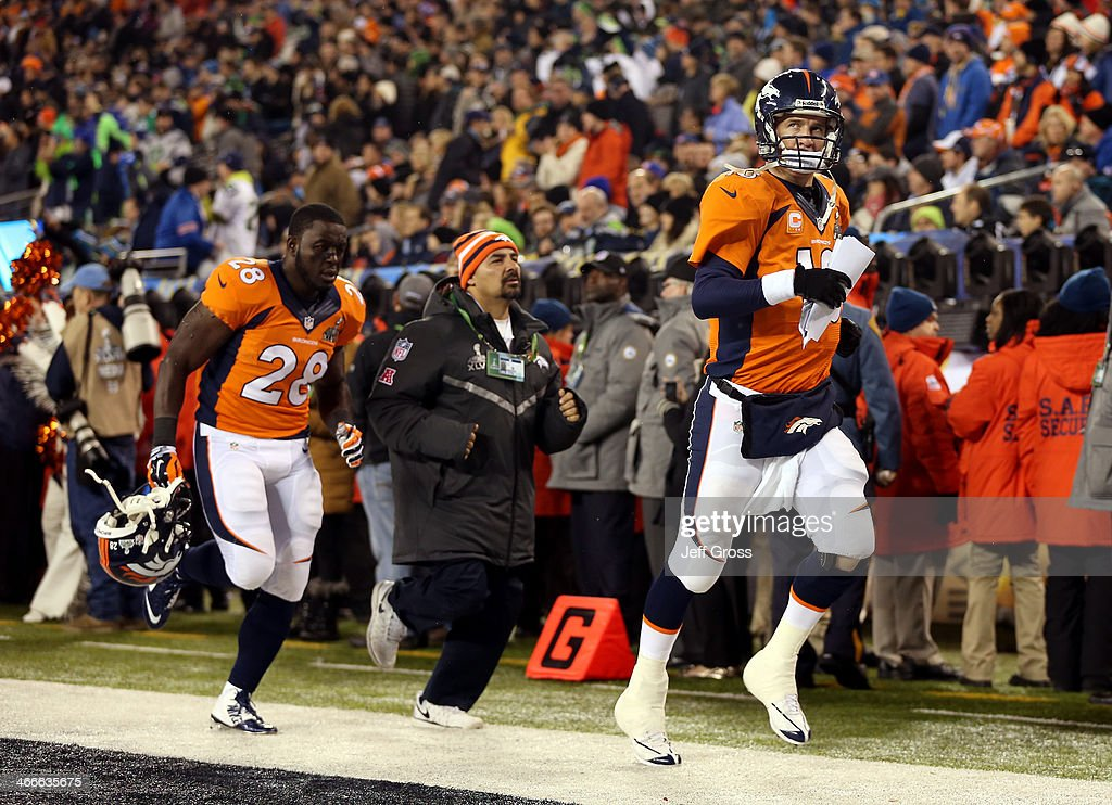 Quarterback Peyton Manning #18 of the Denver Broncos and teammate running back Montee Ball #28 run off the field at the end of the first half against the Seattle Seahawks during Super Bowl XLVIII at MetLife Stadium on February 2, 2014 in East Rutherford, New Jersey.