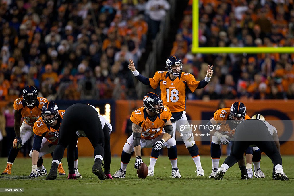 Quarterback <a gi-track='captionPersonalityLinkClicked' href=/galleries/search?phrase=Peyton+Manning&family=editorial&specificpeople=184524 ng-click='$event.stopPropagation()'>Peyton Manning</a> #18 of the Denver Broncos audibles at the line of scrimmage against the New Orleans Saints at Sports Authority Field Field at Mile High on October 28, 2012 in Denver, Colorado.