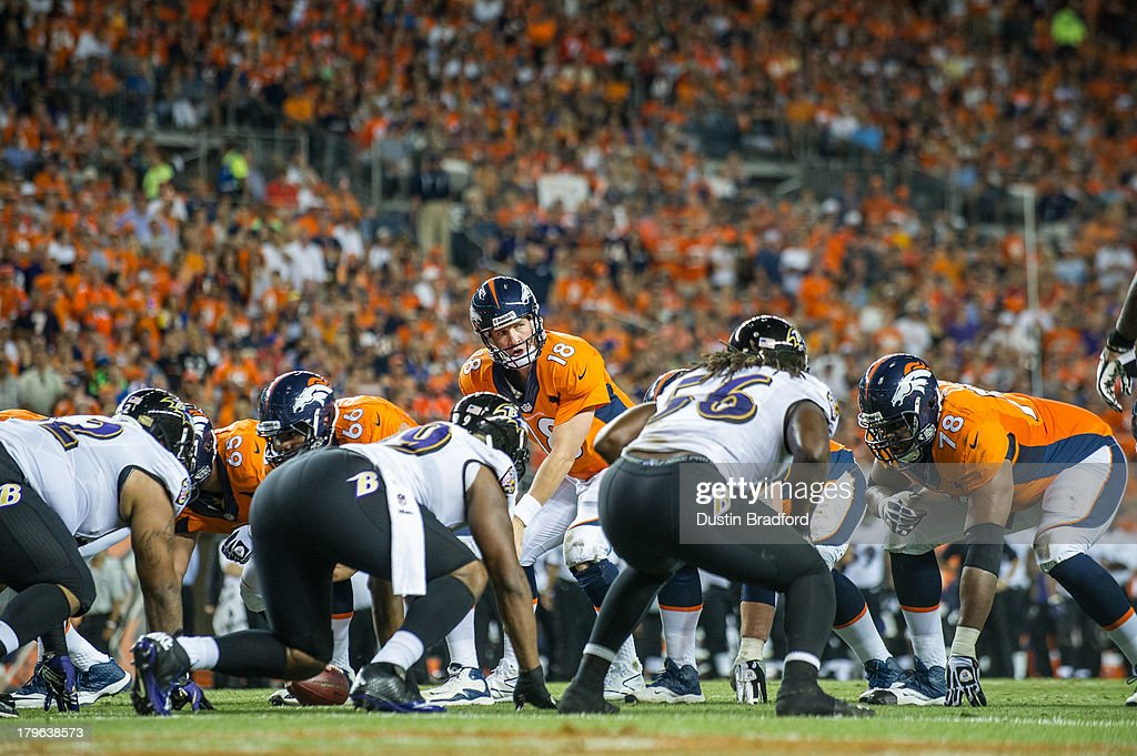 Quarterback <a gi-track='captionPersonalityLinkClicked' href=/galleries/search?phrase=Peyton+Manning&family=editorial&specificpeople=184524 ng-click='$event.stopPropagation()'>Peyton Manning</a> #18 of the Denver Broncos audibles at the line of scrimmage against the Baltimore Ravens during the game at Sports Authority Field at Mile High on September 5, 2013 in Denver Colorado.