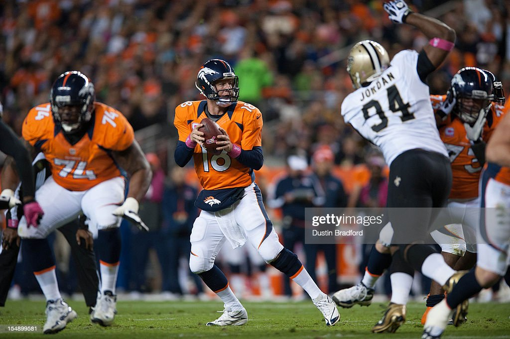 Quarterback <a gi-track='captionPersonalityLinkClicked' href=/galleries/search?phrase=Peyton+Manning&family=editorial&specificpeople=184524 ng-click='$event.stopPropagation()'>Peyton Manning</a> #18 of the Denver Broncos backs up in the pocket to pass during a game against the New Orleans Saints at Sports Authority Field Field at Mile High on October 28, 2012 in Denver, Colorado.