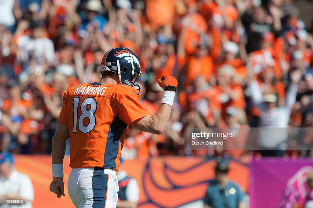 Quarterback Peyton Manning of the Denver Broncos celebrates after passing his 500th career touchdown pass to Julius Thomas in the first quarter of a...