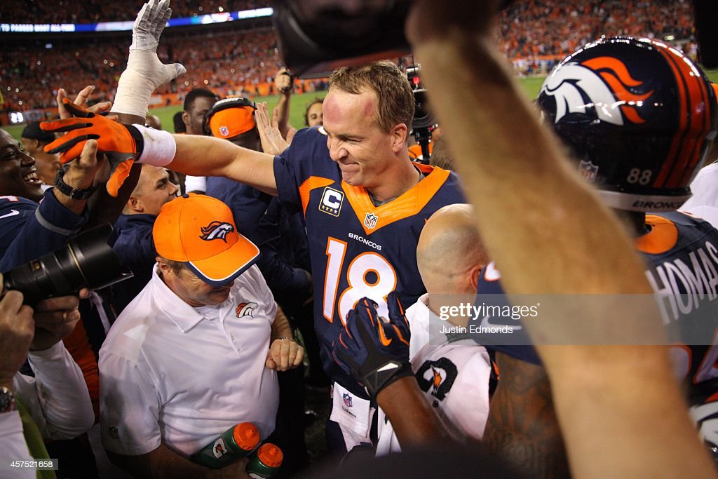 Quarterback Peyton Manning of the Denver Broncos celebrates with teammates and the coaching staff on the sideline after throwing his NFL record 509th...